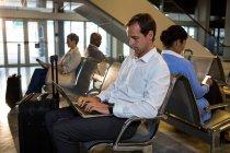 Homme avec bagages à l'aide d'un ordinateur portable dans la salle d'attente à l'aérogare — Photo de stock