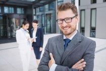 Retrato de um homem de negócios de confiança com braços cruzados sorrindo — Fotografia de Stock