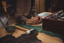 Meia-seção de artesã trabalhando em um pedaço de couro na oficina — Fotografia de Stock