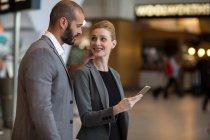 Coppia felice utilizzando il telefono cellulare in aeroporto — Foto stock