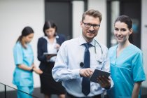 Portrait of smiling doctor and nurse with digital tablet in hospital corridor — Stock Photo