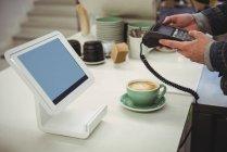 Руки человека с помощью edc машины в биллинг счетчик в кафе — стоковое фото