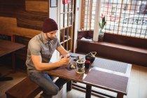 Homme utilisant un téléphone portable dans un restaurant japonais — Photo de stock