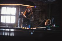 Young happy couple playing pool in bar — Stock Photo