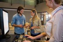 Пара взаємодіють один з одним в на стійці реєстрації в аеропорту терміналу — стокове фото