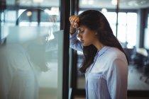 Empresária perturbada encostada à porta do escritório — Fotografia de Stock