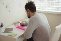 Attentive man writing on document while sitting at desk — Stock Photo