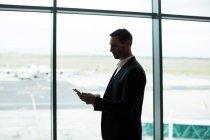 Бизнесмен, использующий цифровой планшет в зоне ожидания в аэропорту — стоковое фото