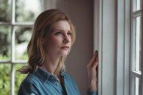 Femme réfléchie regardant par la fenêtre à la femme — Photo de stock