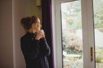 Mujer sonriente tomando café en casa - foto de stock