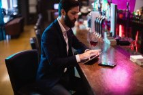 Businessman using digital tablet with wine glass and mobile phone on counter at bar — Stock Photo