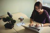 Бизнесвумен работает на ноутбуке в офисном интерьере — стоковое фото