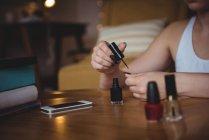 Woman applying nail polish at home — Stock Photo