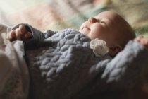 Крупный план милый ребенок лежит на кровати в спальне дома — стоковое фото