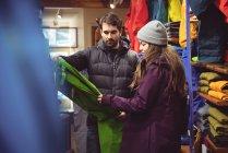 Casal selecionando vestuário juntos em uma loja de roupas — Fotografia de Stock