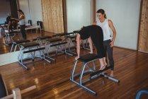 Istruttore che assiste la donna durante la pratica di pilates in palestra — Foto stock