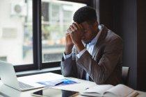 Uomo d'affari che si siede alla sua scrivania nell'ufficio sollecitato — Foto stock