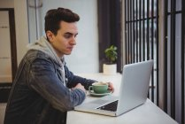 Uomo guardando il computer portatile mentre tiene il caffè in caffetteria — Foto stock