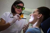 Dentista examinando dientes jóvenes con luz de curado dental en la clínica - foto de stock