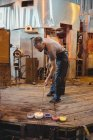 Glassblower attaching colored glass to a piece of hot molten glass at glassblowing factory — Stock Photo