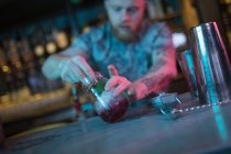 Bartender preparing cocktail at counter in bar — Stock Photo