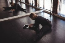 Dancer stretching on floor and using mobile phone in dance studio — Stock Photo