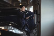 Man talking on mobile phone while charging electric car in garage — Stock Photo