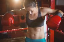 Tired female boxer leaning on boxing ring in fitness studio — Stock Photo