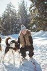 Woman petting Siberian dog during winter — Stock Photo