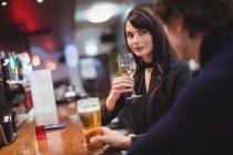 Couple prenant un verre ensemble au bar — Photo de stock