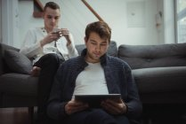 Gay couple using mobile phone and digital tablet in living room at home — Stock Photo