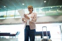 Femme d'affaires utilisant une tablette numérique dans la salle d'attente au terminal de l'aéroport — Photo de stock