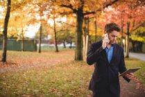 Empresário falando no celular e segurando tablet digital no parque — Fotografia de Stock