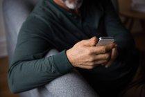 Средняя часть человека с помощью мобильного телефона в гостиной на дому — стоковое фото
