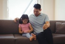 Father and daughter using digital tablet in living room at home — Stock Photo