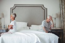 Senior man and woman sitting on bed and ignoring each other in bed room — Stock Photo