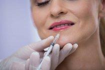 Primo piano della donna adulta di mezza età che riceve un'iniezione di botox in clinica — Foto stock