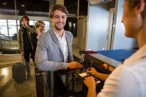Geschäftsmann in der Warteschlange erhält Pass und Bordkarte am Flughafenterminal — Stockfoto