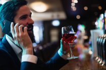 Businessman talking on mobile phone while having glass of wine in bar — Stock Photo
