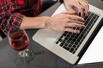 Hands of man using laptop with wine glass on table in bar — Stock Photo