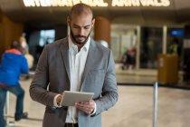 Empresario con tableta digital en sala de espera en terminal del aeropuerto - foto de stock