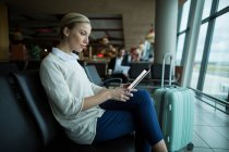 Female commuter using digital tablet in the waiting area at airport — Stock Photo