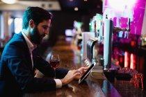 Uomo d'affari che utilizza tablet digitale con bicchiere di vino sul bancone nel bar — Foto stock
