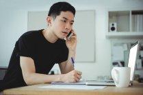 Ejecutivo de negocios escribiendo en el diario mientras habla en el teléfono móvil en la oficina - foto de stock