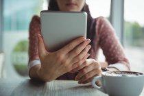 Seção média da mulher usando tablet digital enquanto toma uma xícara de café no café — Fotografia de Stock