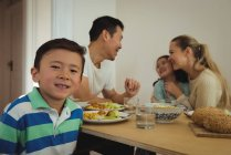 Portrait de garçon souriant tout en ayant des repas en arrière-plan à la maison de famille — Photo de stock