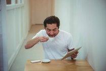 Uomo che utilizza tablet digitale mentre prende il caffè in caffetteria — Foto stock