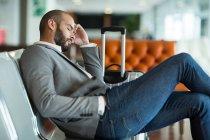 Uomo d'affari che dorme sulla sedia in sala d'attesa al terminal dell'aeroporto — Foto stock