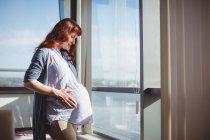 Mujer embarazada reflexiva de pie cerca de la ventana en la sala de estar en casa - foto de stock