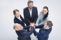 Porträt von Geschäftsleuten, die sich im Büro die Hände stapeln — Stockfoto